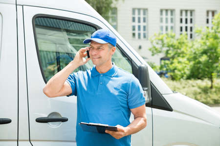 delivery truck: Young Happy Male Worker In Front Of Truck Writing On Clipboard Stock Photo