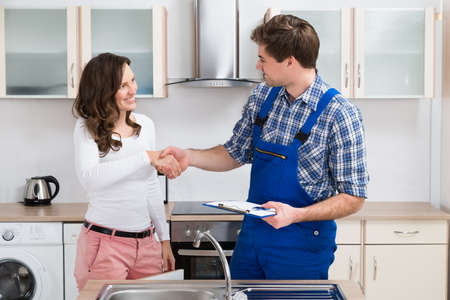 Young Woman Shaking Hands To Male Plumber With Clipboard In Kitchen Room Stockfoto