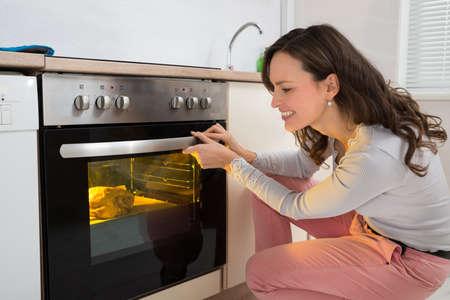 Happy Woman Roasting Chicken Meat In Kitchen Oven Zdjęcie Seryjne - 43082335