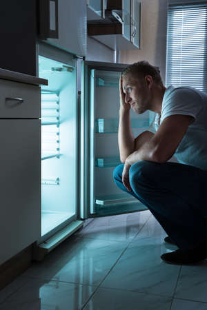 Young Man Looking For Food In Empty Fridge At Nighttime