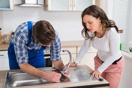 fontanero: Mujer joven que mira la Fontanero fijaci�n de acero Tap En fregadero de cocina Foto de archivo