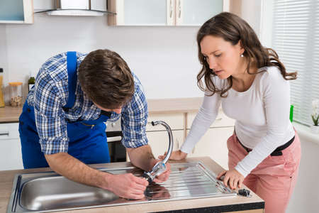fixing: Young Woman Looking At Plumber Fixing Steel Tap In Kitchen Sink