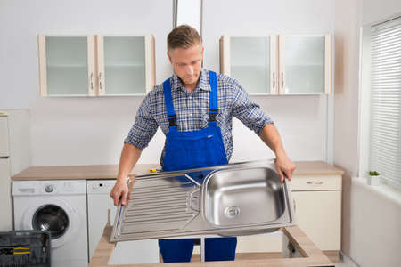 plumber: Male Plumber Fixing Stainless Steel Sink In Kitchen