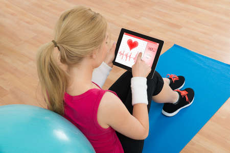 rate: Young Woman Looking At Heart Pulse Rate On Digital Tablet In Living Room Stock Photo
