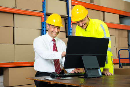Portrait Of Happy Warehouse Worker And Manager Using Computer In A Warehouse