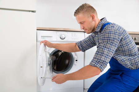 overall: Young Male Technician In Overall Fixing Washing Machine