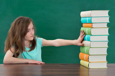 rejection sad: Portrait Of Girl Touching Multi-colored Stack Of Books At The Table
