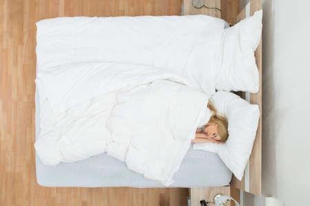 cama: Opinión de alto ángulo la mujer joven que duerme en cama con Manta Foto de archivo