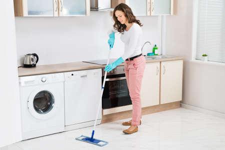 limpieza  del hogar: Mujer feliz con la fregona del piso de limpieza en la cocina en el hogar Foto de archivo