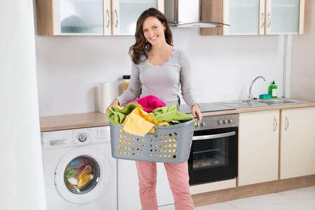 lavanderia: Feliz mujer que lleva la cesta de lavadero en cocina Sala
