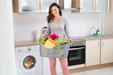 basket: Happy Woman Carrying Laundry Basket In Kitchen Room