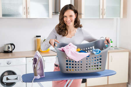 the iron lady: Happy Woman With Electric Iron And Basket With Clothes On Ironing Board Stock Photo