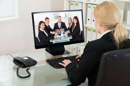people watching: Young Businesswoman At Desk Video Conferencing With Colleagues On Computer In Office