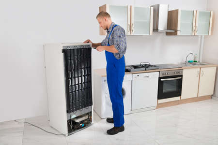 overall: Young Repairman In Overall Repairing Refrigerator In Kitchen Room Stock Photo