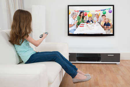 Girl Changing Channel With Remote Control In Front Of Television At Home