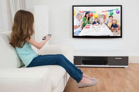Menina mudar de canal com controle remoto na frente da televisão em casa