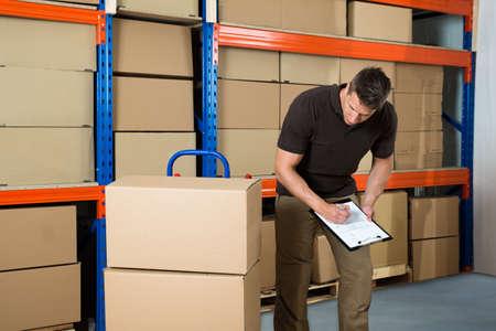 obrero trabajando: Trabajador de sexo masculino con cajas de cartón escrito en el portapapeles en almacén Foto de archivo