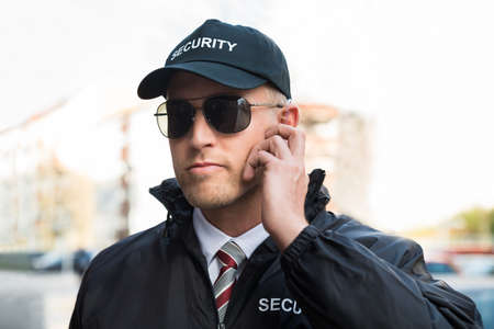 security uniform: Portrait Of Young Male Security Guard Listening To Earpiece Stock Photo