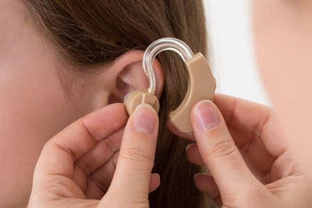 niños discapacitados: Primer plano de audífono Médico Inserción en el oído de una chica