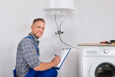 installation: Male Plumber Smiling While Writing Meter Reading Of Electric Boiler On Clipboard
