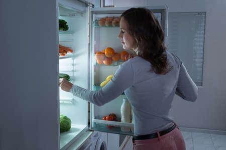 refrigerador: Joven y bella mujer en busca de comida en la nevera