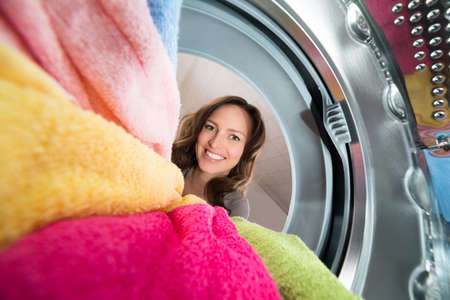 work load: Close-up Of Happy Woman View From Inside The Washer With Clothes