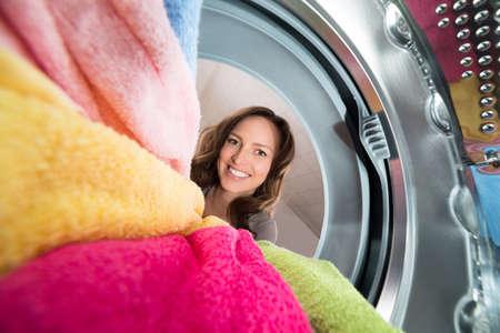 carga: Primer De La Mujer Feliz Vista del interior de la lavadora con ropa