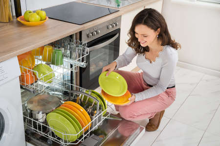 daily room: Young Happy Woman Arranging Plates In Dishwasher At Home