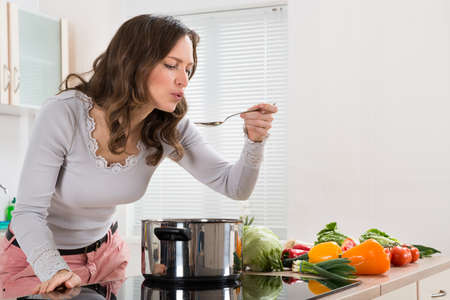 Young Woman Tasting Food With Spoon In Kitchen Stock Photo