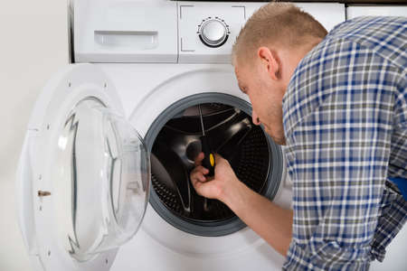 overall: Young Worker In Overall Fixing Washing Machine In House