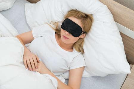 dormir: Mujer joven que duerme con la máscara del sueño en el dormitorio