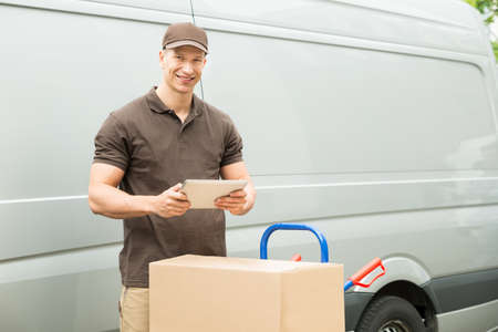 deliveryman: Young Happy Delivery Man With Digital Tablet And Cardboard Boxes Stock Photo