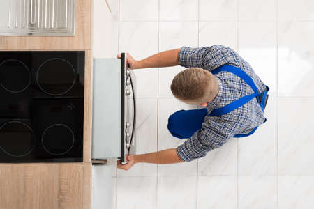 High Angle View Of Man In Overall Repairing Oven In Kitchen