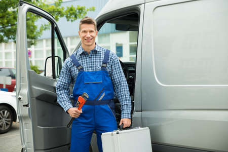 fontanero: Happy Male Worker With Work Tool And Toolbox In Front Of Van