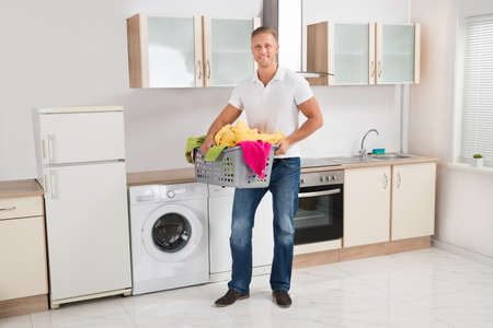 laundry room: Young Happy Man Carrying Multi-colored Clothes In Laundry Basket In Kitchen Room Stock Photo