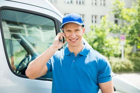 Happy Male Worker In Front Truck Talking On Mobile Phone Standard-Bild