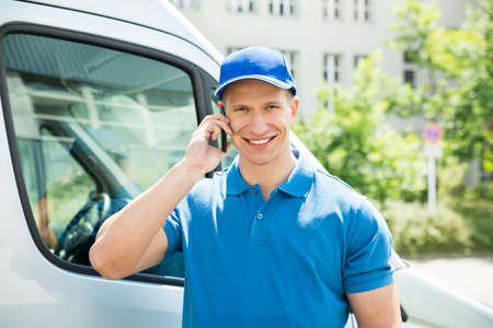 Happy Male Worker In Front Truck Talking On Mobile Phone Stock Photo