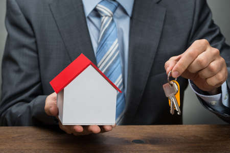 doorkey: Close-up Of Businessman Hands With Keys And House Model Stock Photo