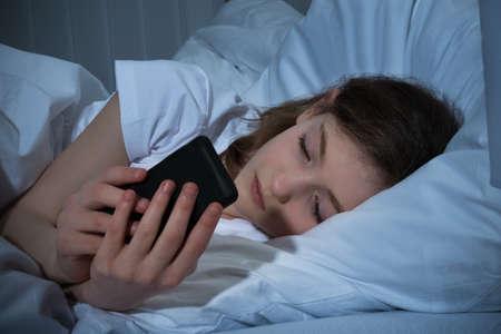 침대에 누워있는 동안 밤에 휴대 전화에 문자 메시지 소녀