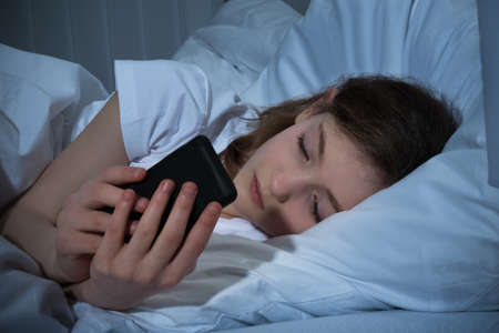 cellular telephone: Girl Texting On Mobile Phone At Night While Lying In Bed