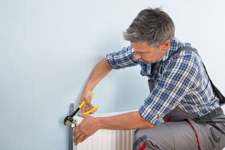 plumber: Portrait Of Male Plumber Fixing Radiator With Wrench