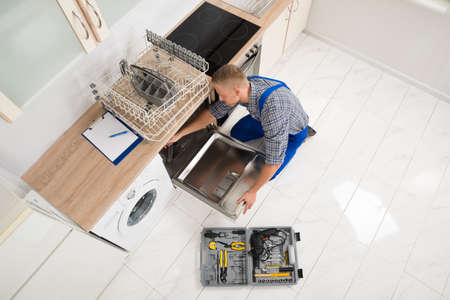 toolbox: High Angle View Of Male Worker With Toolbox Repairing Dishwasher In Kitchen Room