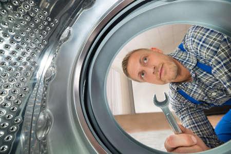 lavado: Reparador joven con la llave inglesa Mirando dentro de la lavadora