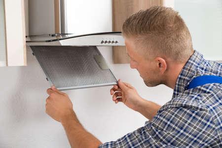 extractor: Young Repairman Repairing Kitchen Extractor Filter In Kitchen Room