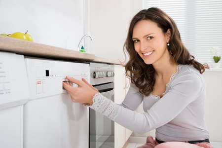 Happy Woman Opening Dishwasher In Kitchen Room