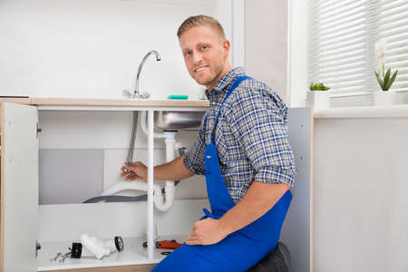 Happy Male Plumber Repairing Faucet In Kitchen Sink
