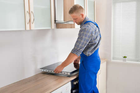 repairman: Young Repairman Installing Induction Cooker In Kitchen