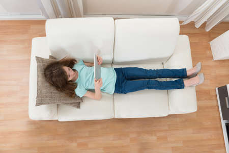 overhead: High Angle View Of Girl Lying On Sofa Using Digital Tablet In Living Room