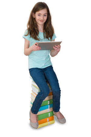 tablet computer: Girl With Digital Tablet Sitting On Multi-colored Stack Of Books Over White Background
