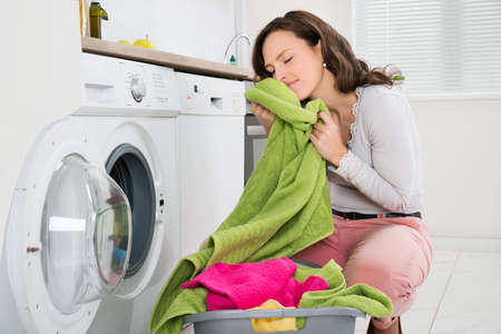 casual clothing: Young Woman Crouching With Cleaned Clothes Near The Electronic Washer